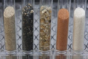 five glass testing tubes with different sand samples collected from beaches and deserts of western USA and Hawaii